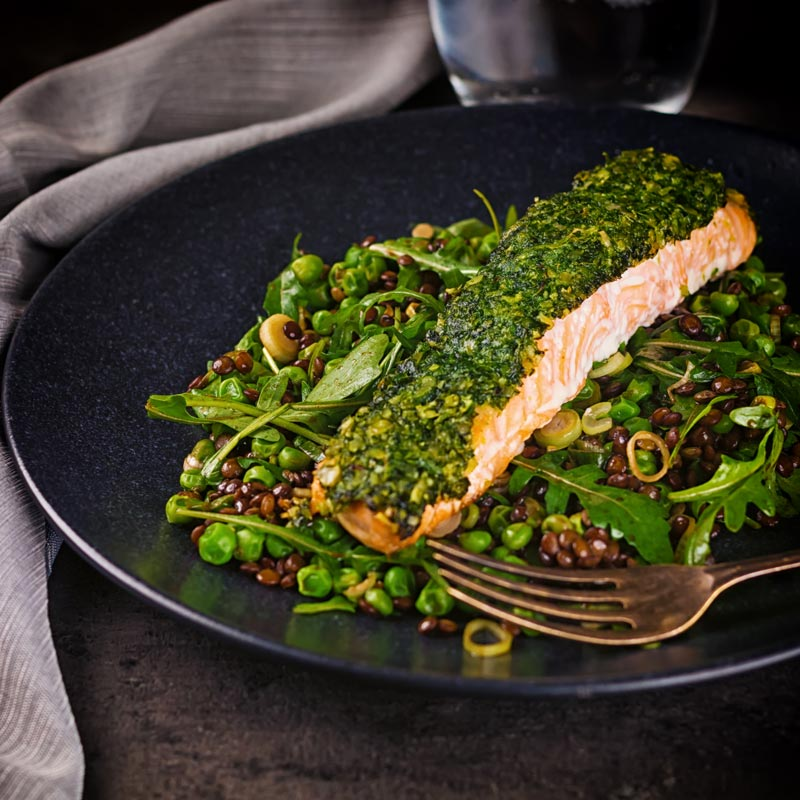 Square image of a baked salmon filllet with a green herby crust on a lentil salad against a dark backdrop