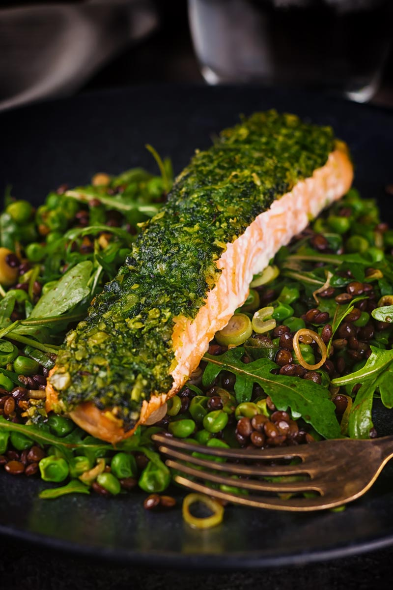 Tall image of baked salmon filllet with a green herby crust on a lentil salad against a dark backdrop