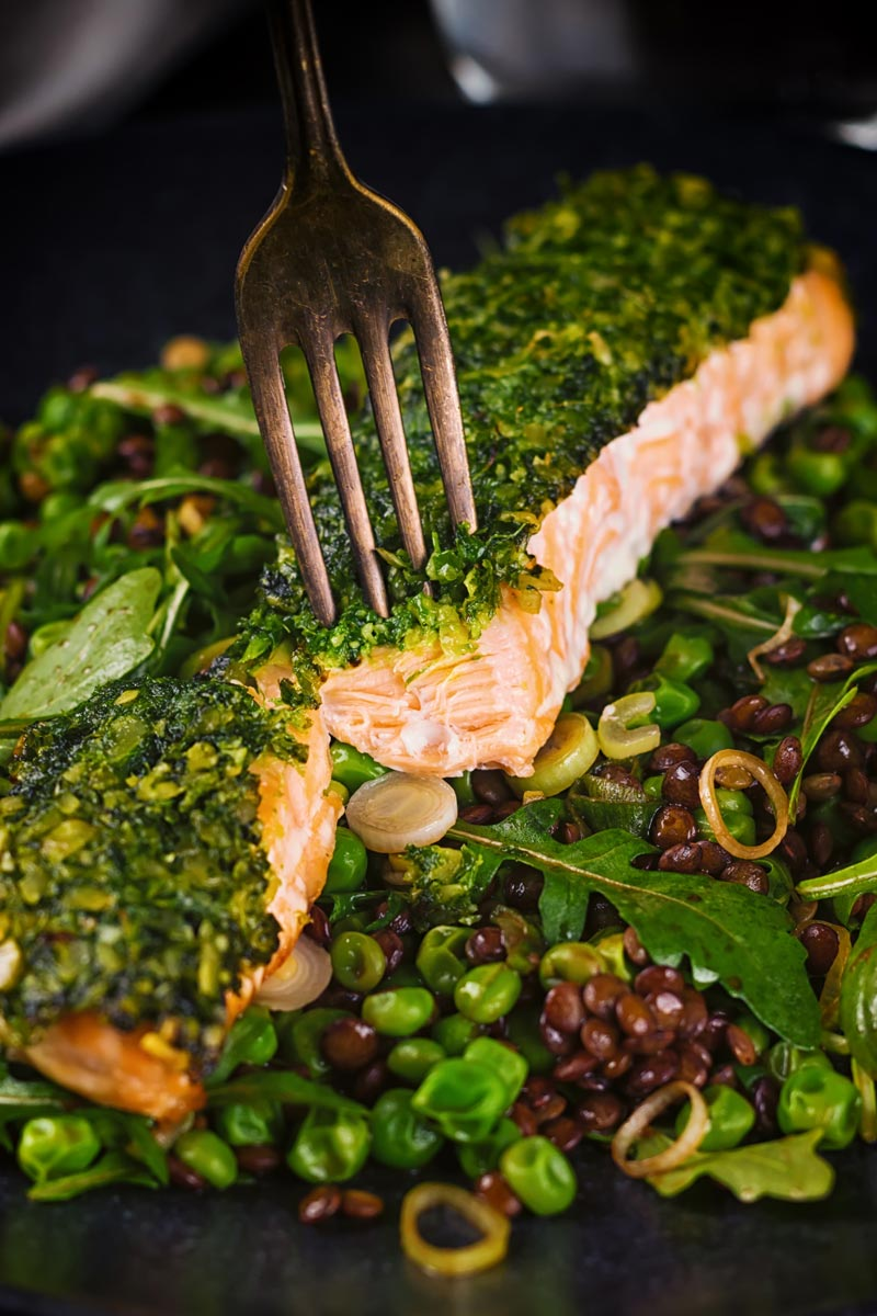 Tall image of a baked salmon filllet with a green herby crust  with a fork showing the interior of the salmon