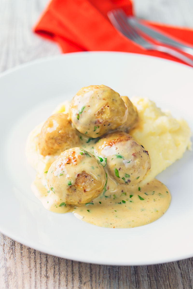Portrait image of chicken meatballs in a honey and mustard sauce on mashed potatoes served on a white plate.