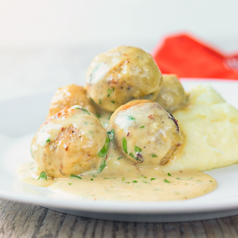 Square image of chicken meatballs in a honey and mustard sauce on mashed potatoes served on a white plate.
