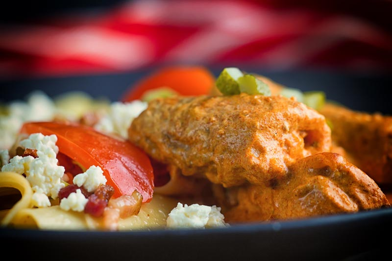 Close up landscape image of catfish paprikash with tomatoes and a pasta side dish