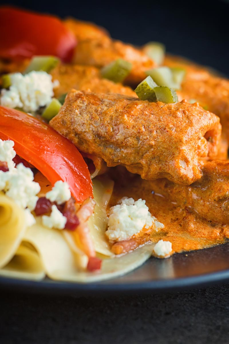 Close up tall image of catfish paprikash with tomatoes and a pasta side dish