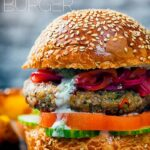 Portrait close up image of an Indian inspired spicy lamb burger with a red onion chutney and a text overlay