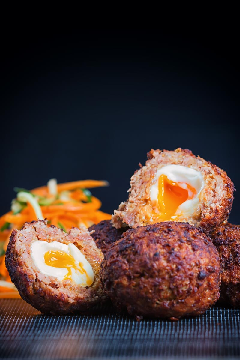 Portrait image of a Nargis kebab or Indian Scotch Eggs in a pile featuring one cut open showing a runny yolk