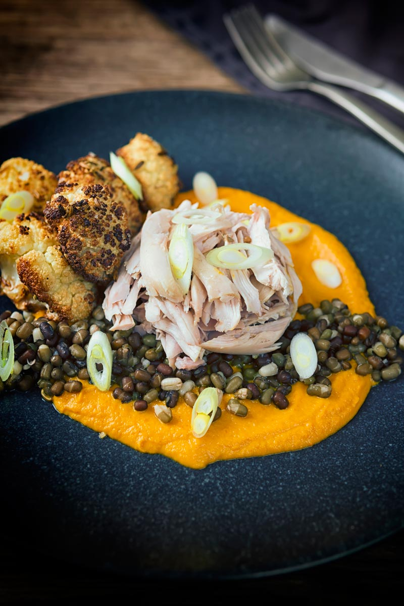 Portrait image of shredded slow cooked rabbit legs with mung beans, roasted cauliflower and spiced carrot puree on a dark plate