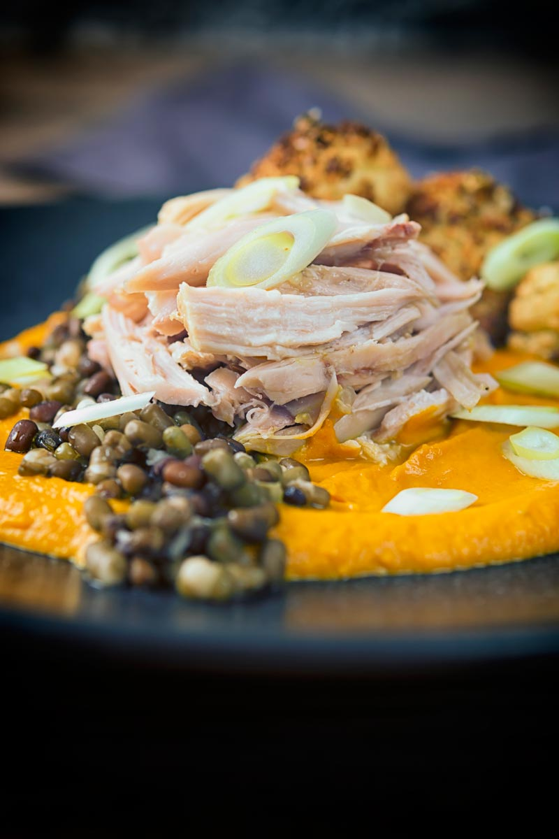 Portrait image of shredded slow cooked rabbit legs with mung beans and spiced carrot puree on a dark plate