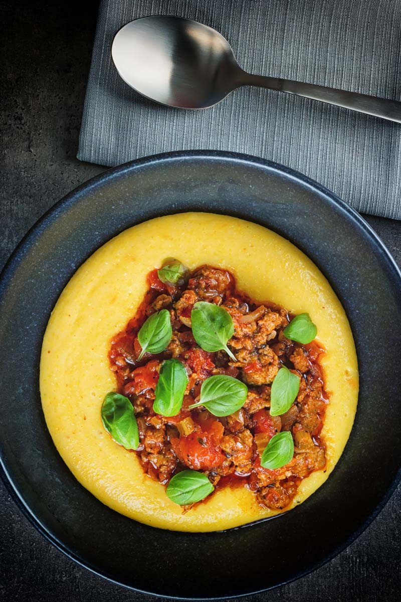 Portrait image taken from above of a Italian sausage ragu served on a vibrant polenta served in a black bowl