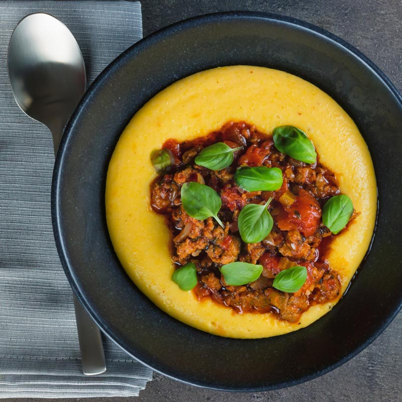 Square image taken from above of an Italian sausage ragu served on a vibrant polenta served in a black bowl