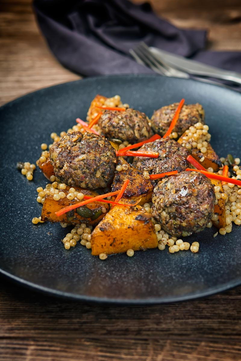Portrait image of roasted butternut squash and Israeli couscous with Lamb kofta and chili batons served on a black plate