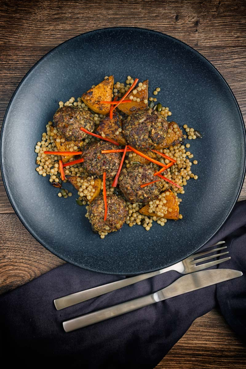 Portrait image of roasted butternut squash and Israeli couscous with Lamb kofta and chili batons served on a black plate taken from above