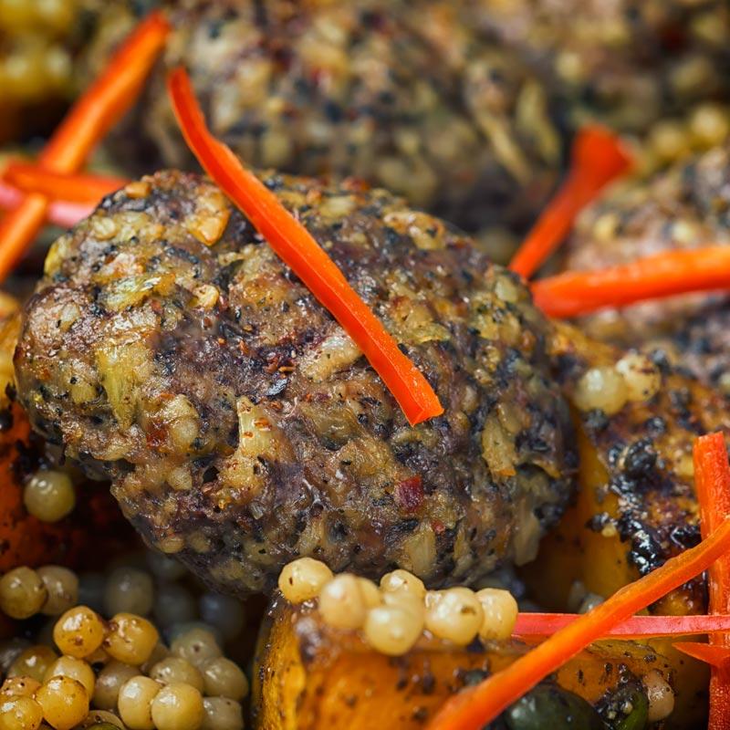 Square close up image of Lamb kofta, Israeli couscous and chili batons