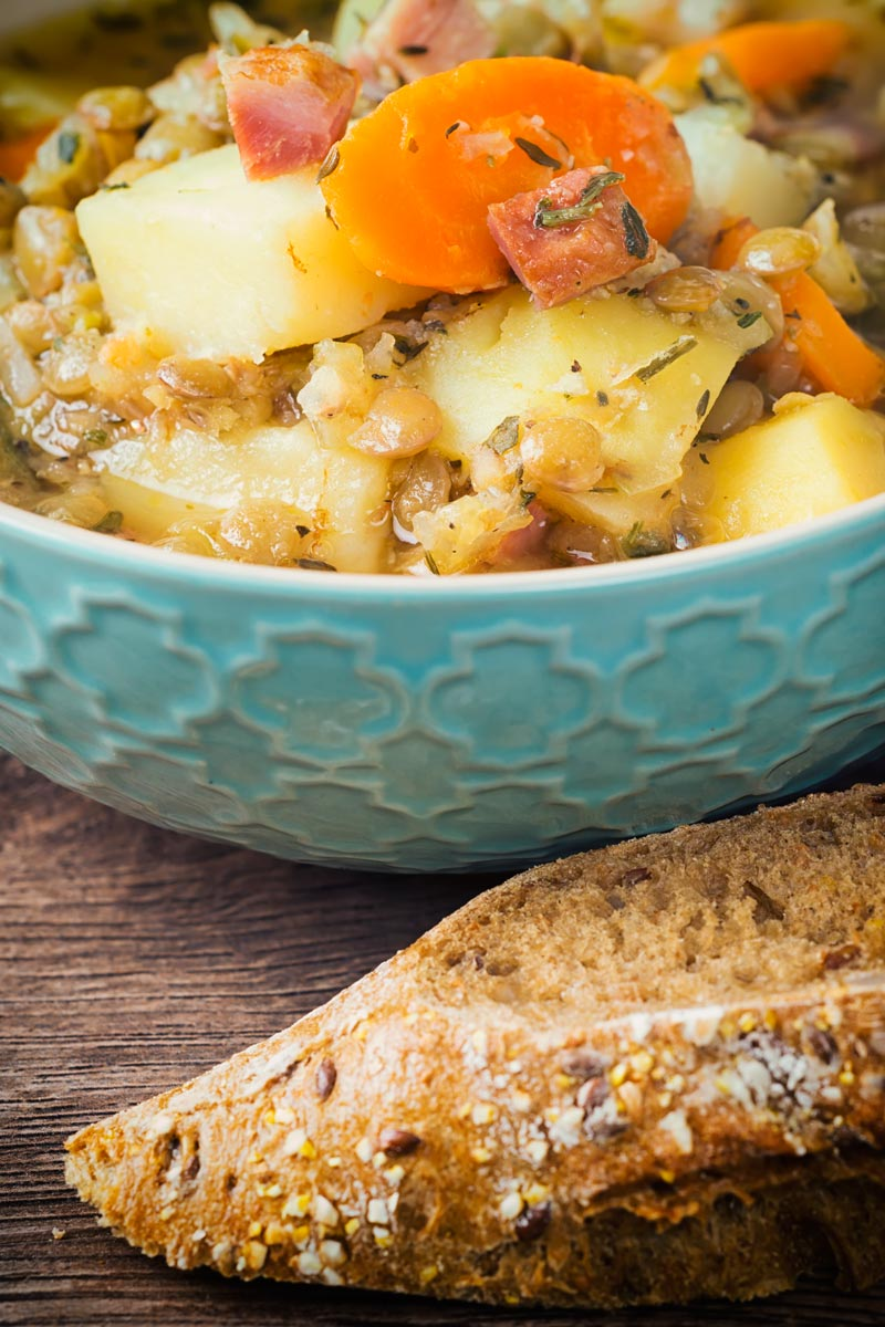 Tall image of a lentil and bacon soup in a patterned light blue bowl with some seeded bread