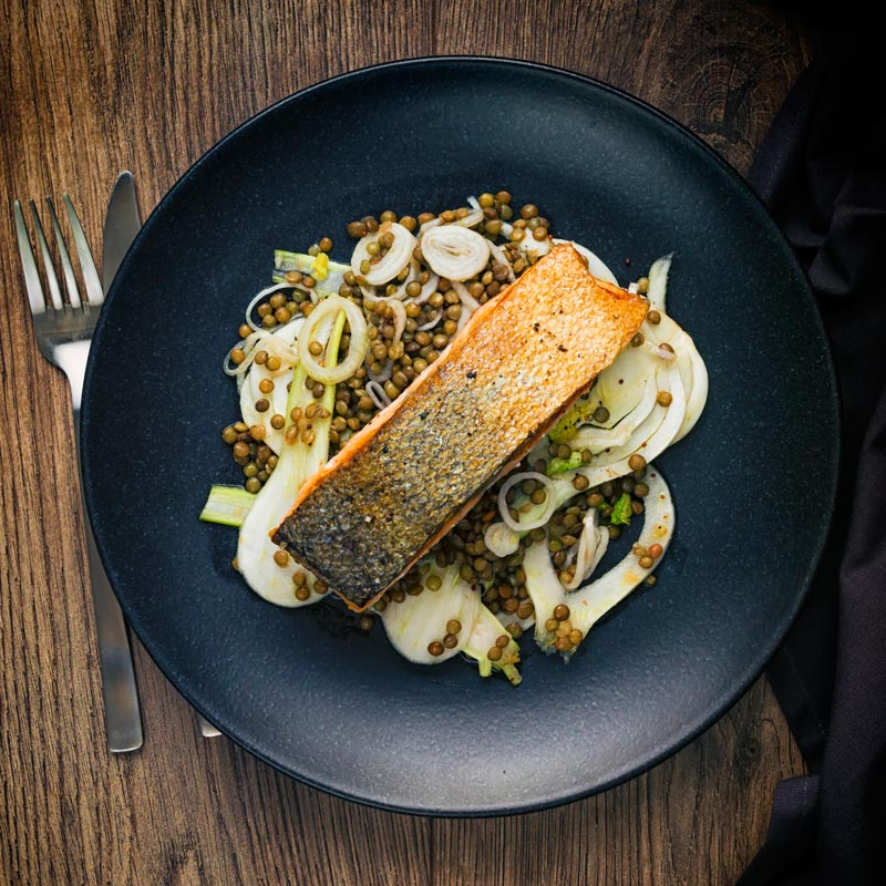 Square image of pan fried salmon with crispy skin served on lentils with pickled fennel on a black plate taken from above