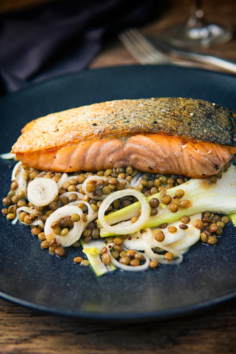 Tall image of pan fried salmon with crispy skin served on lentils and pickled fennel on a black plate