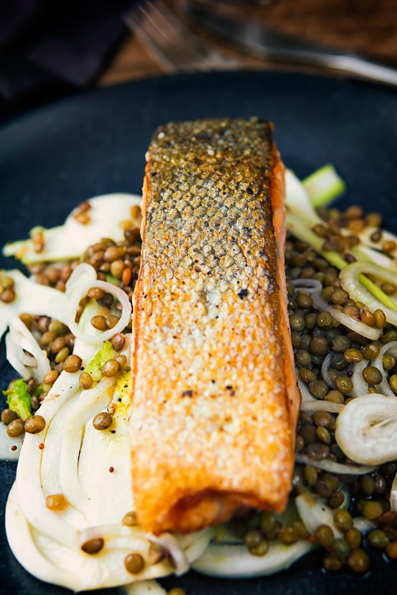 Tall image of pan fried salmon with lentils and pickled fennel against a dark backdrop