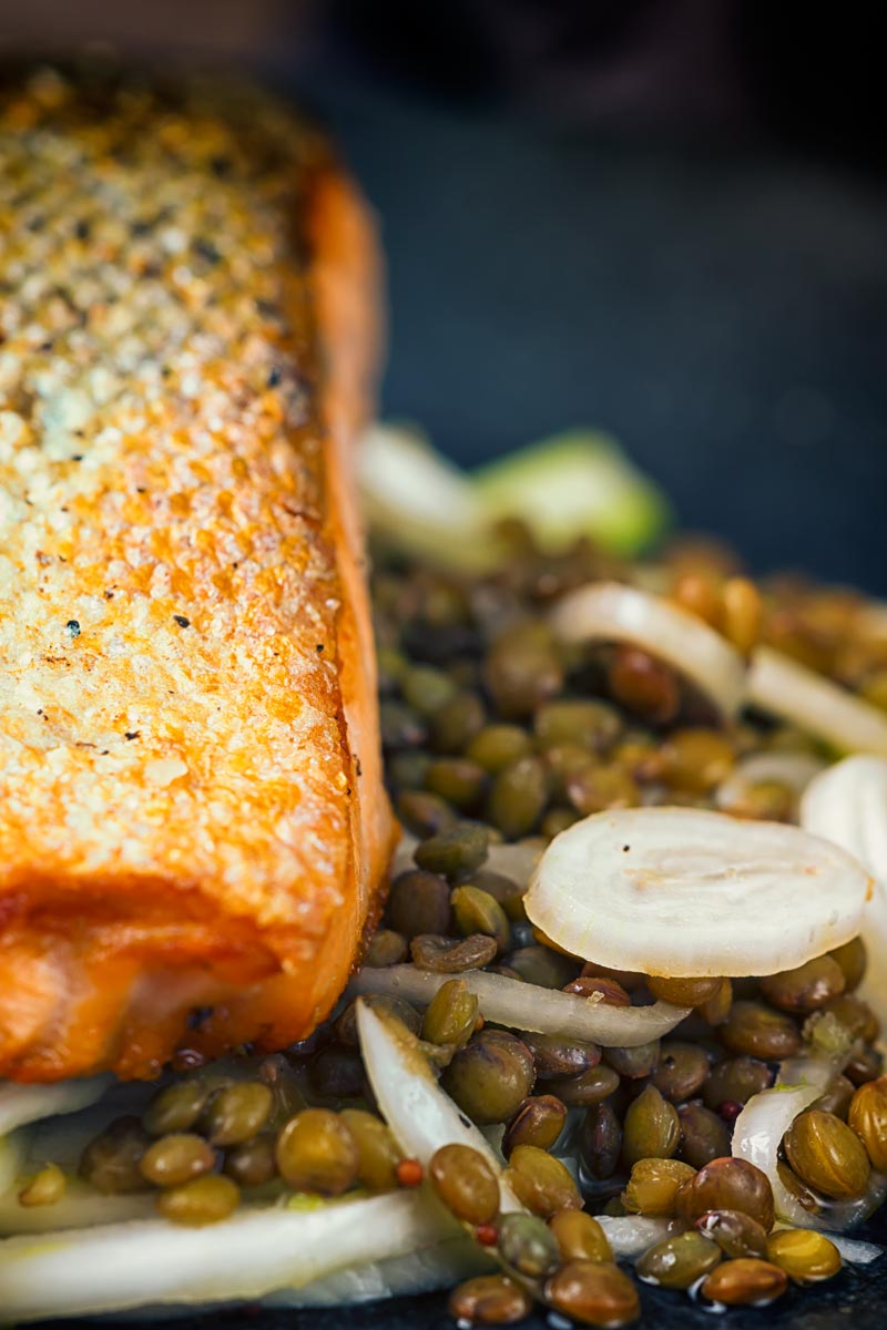 Close up tall image of pan fried salmon with lentils and pickled fennel against a dark backdrop