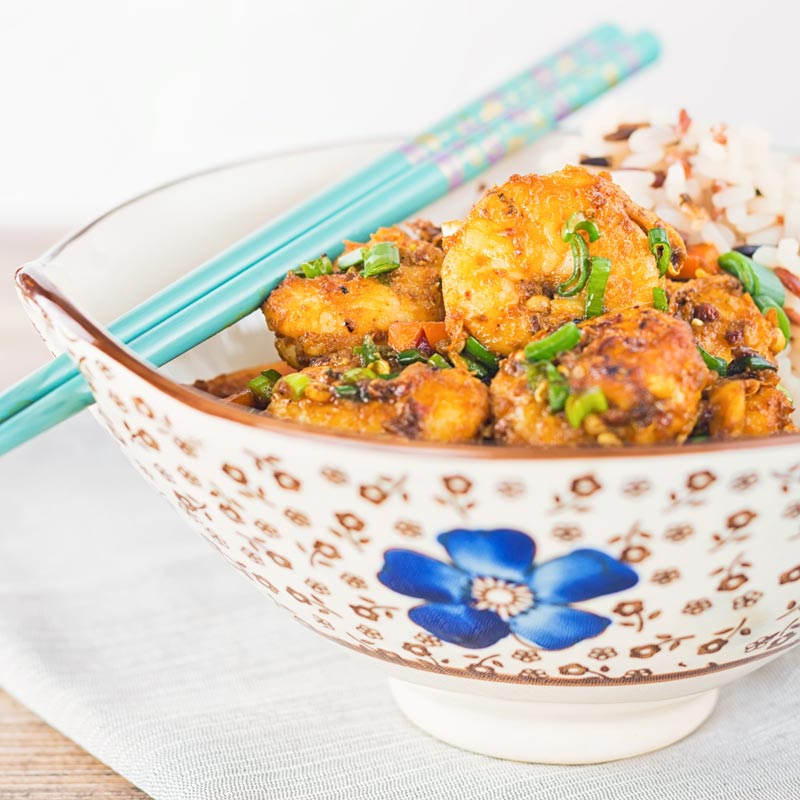 Square image of shrimp stir fry in an Asian style bowl with a blue flower