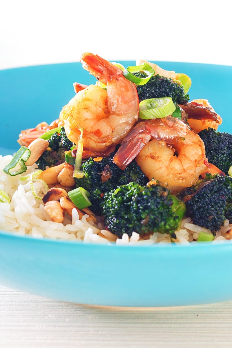 Close up tall image of teriyaki shrimp in a blue bowl with broccoli and white rice