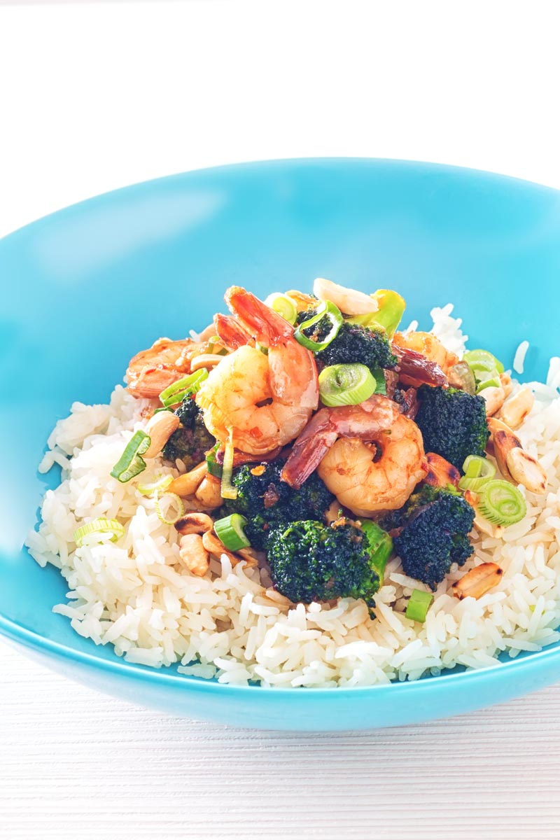 Tall image of teriyaki shrimp in a blue bowl with broccoli and white rice