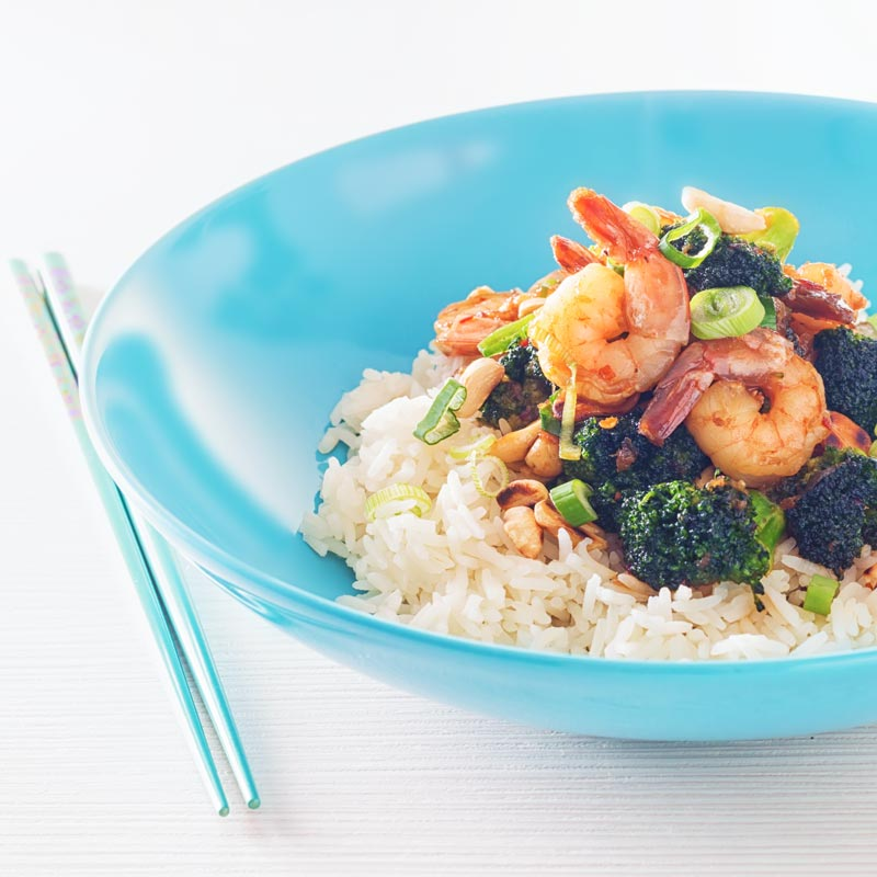 Square image of teriyaki shrimp in a blue bowl with broccoli and white rice