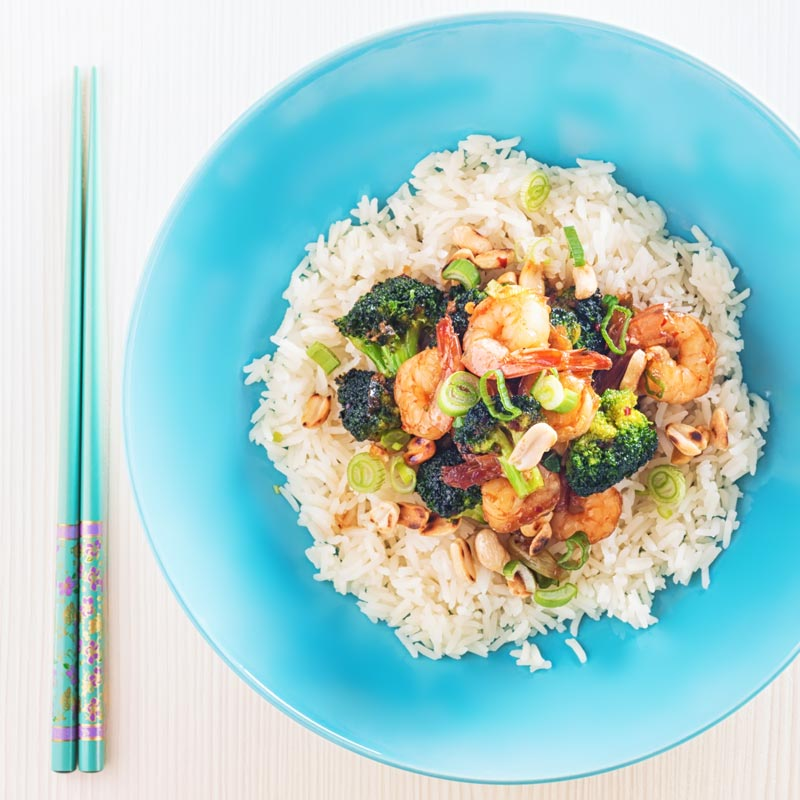 Square image taken from above of teriyaki shrimp in a blue bowl with broccoli and white rice