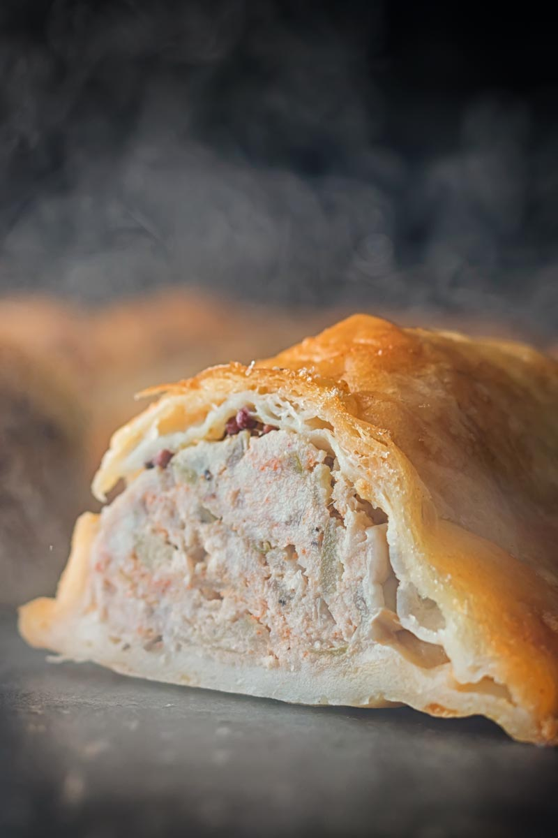 Tall close up image of the interior of a shortcrust pastry wrapped sausage roll