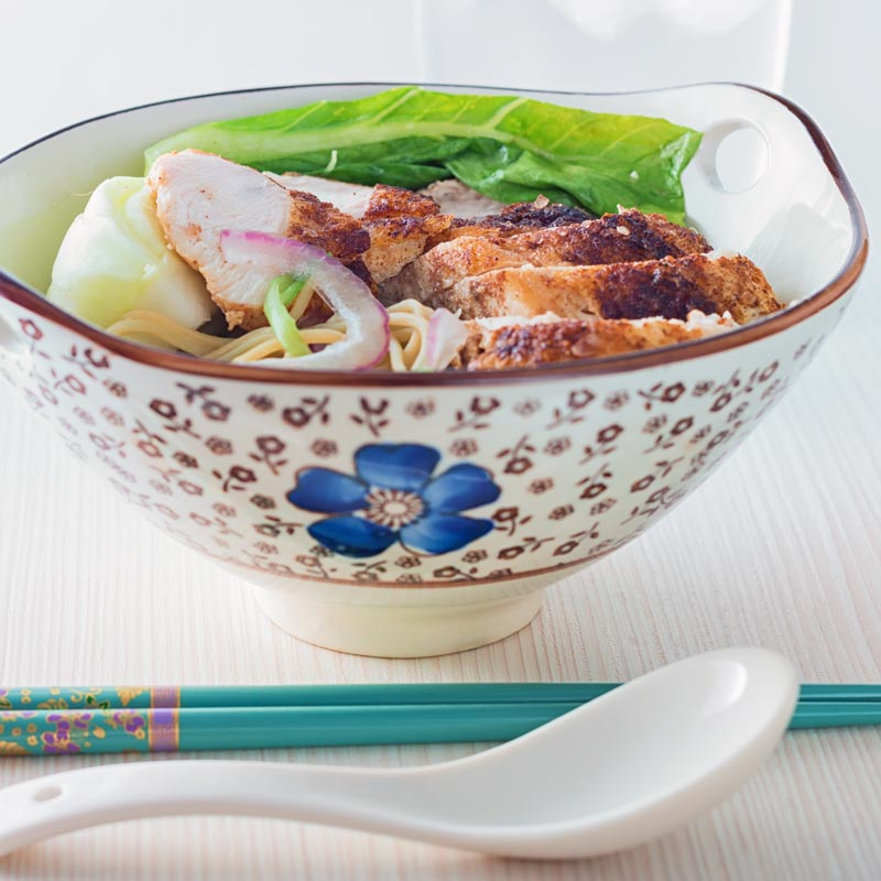 Square image of a Chinese chicken noodle soup in an Chinese style bowl with a blue flower