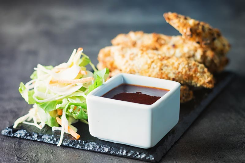 White bowl of sauce with crispy chicken tenders in the background