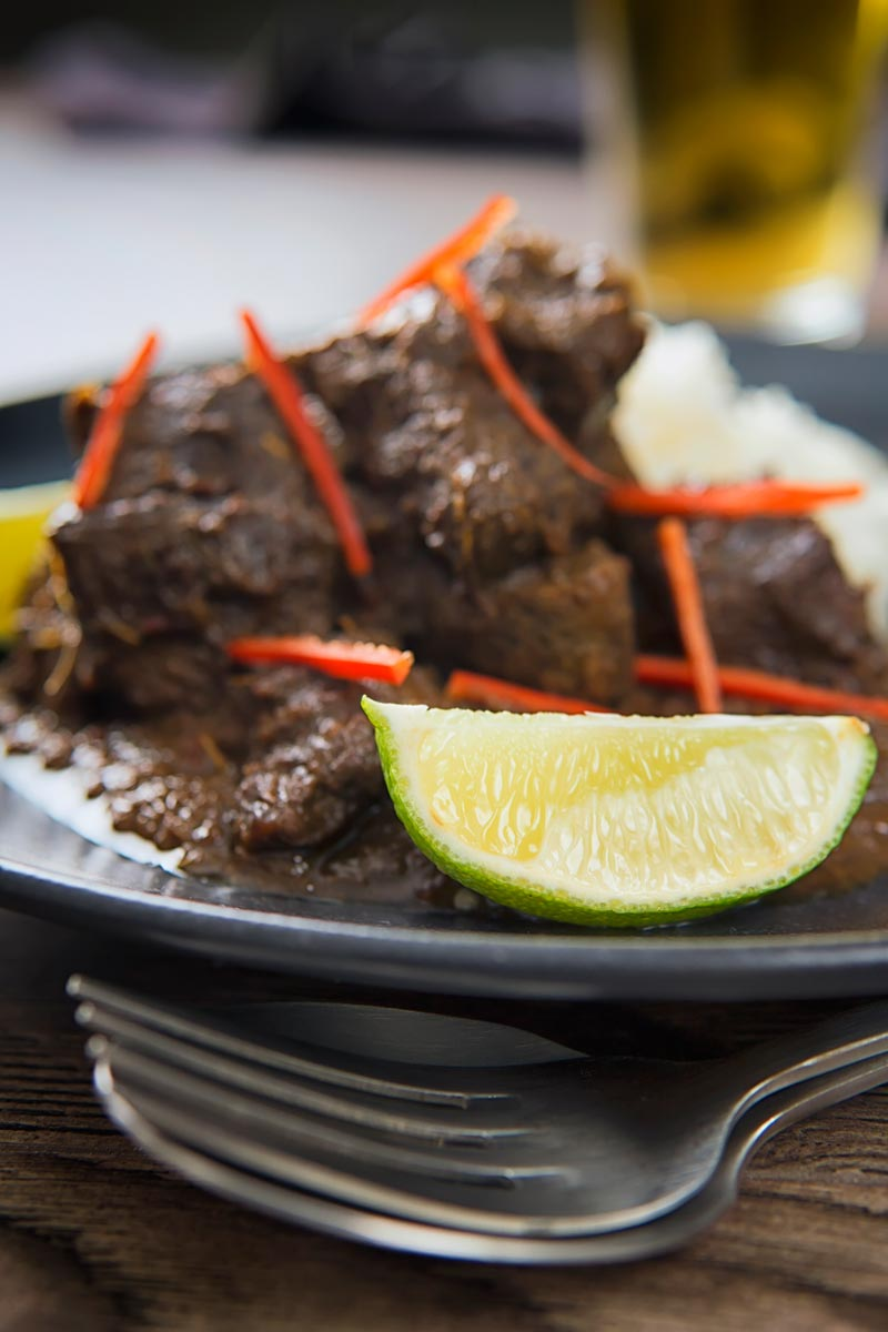 Close up portrait image of alime wedge served in front of an out of focus beef rendang with red chilli ribbons.