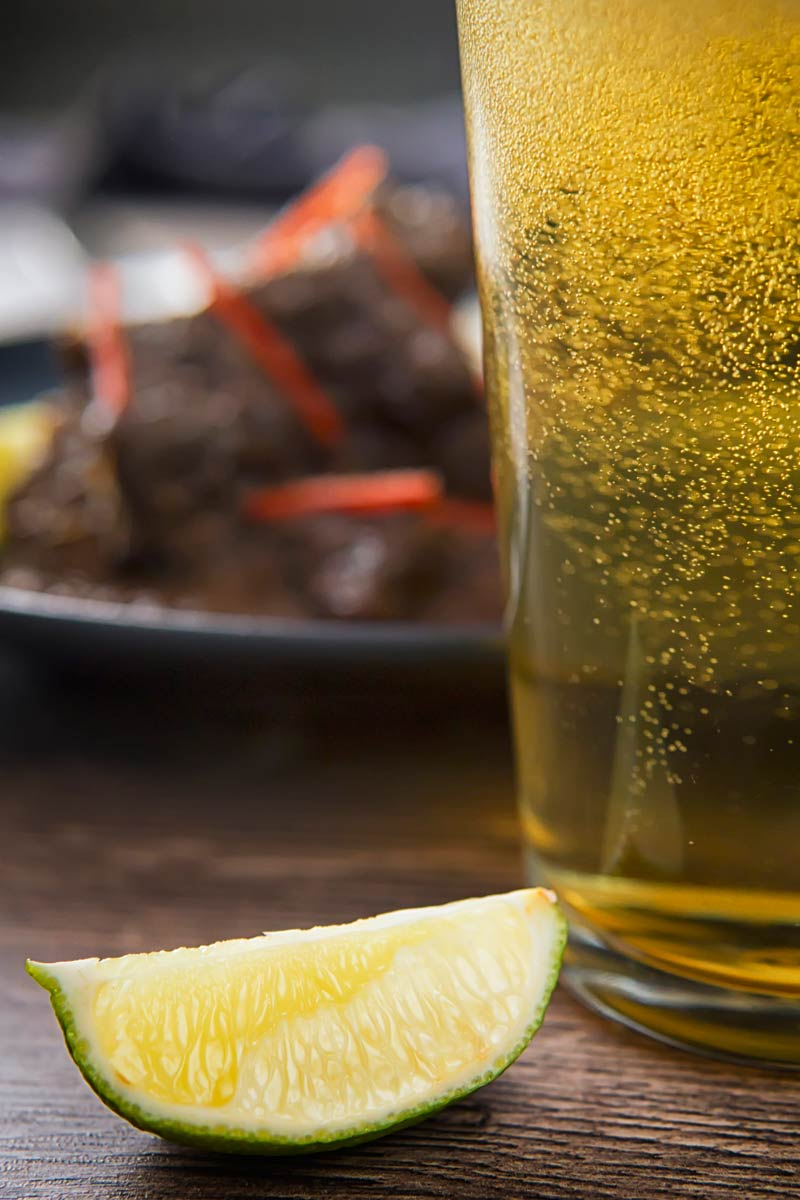 Close up tall partial image if a freshly poured beer and a wedge of lime with out of focus beef rendang in the background