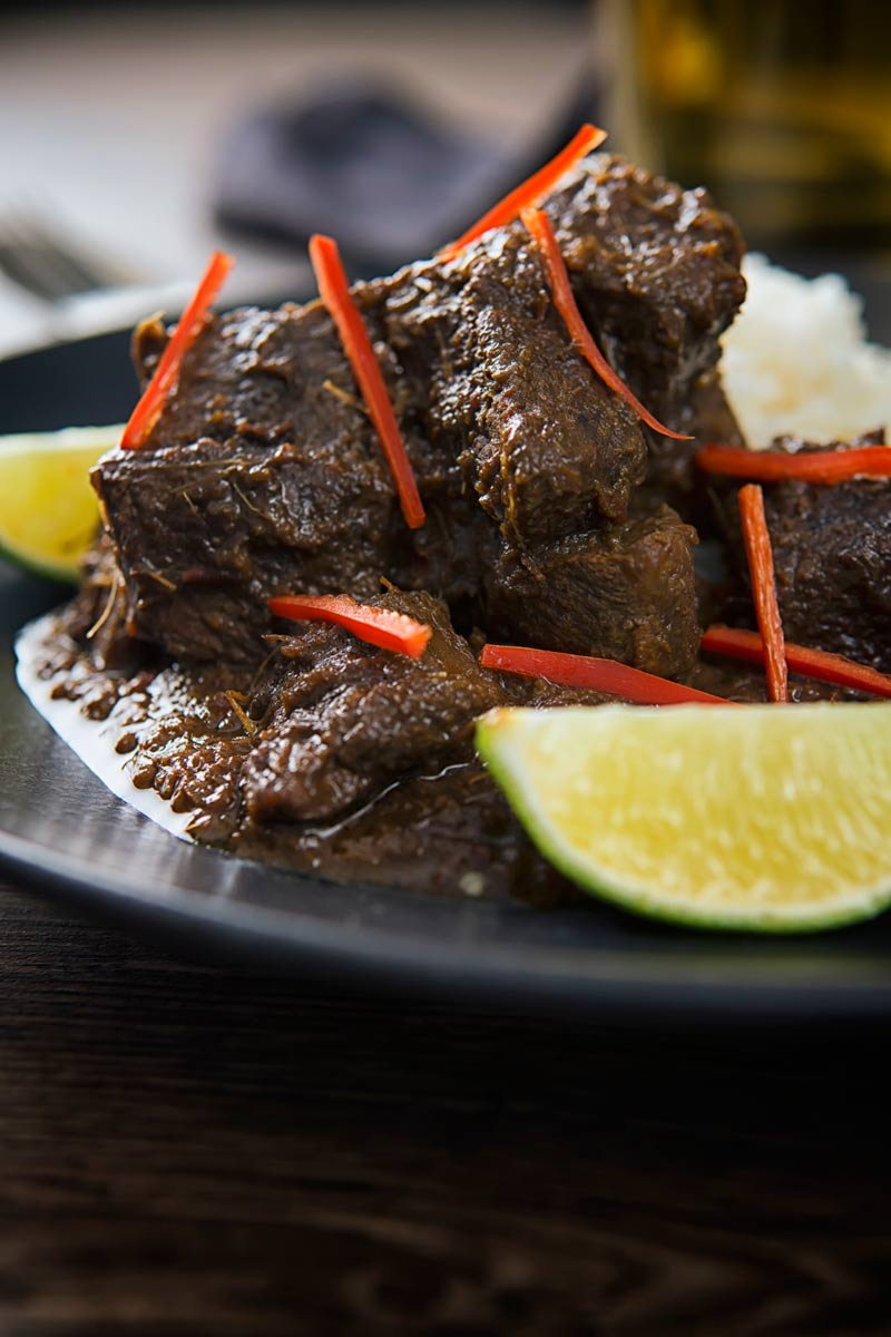Close up portrait of an Indonesian Beef Rendang served on a black plate with rice, lime wedges and chilli ribbons.