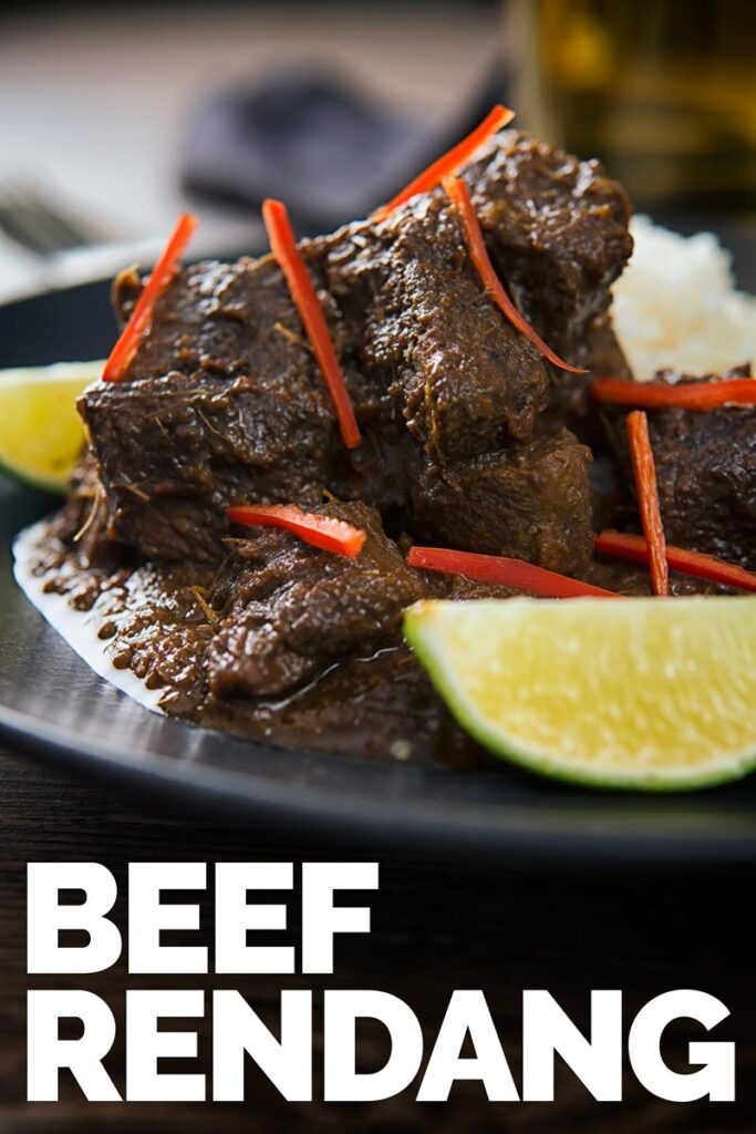 Close up tall image of beef rendang with chili pepper ribbons and lime wedges