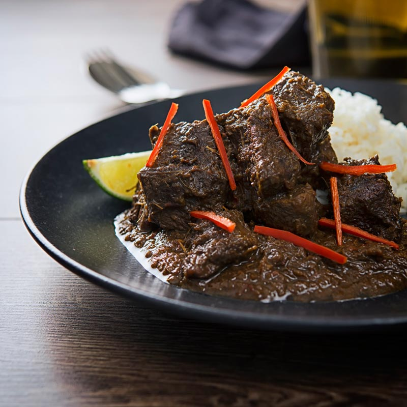 Square image of an Indonesian Beef Rendang served on a black plate with rice, lime wedges and chilli ribbons.