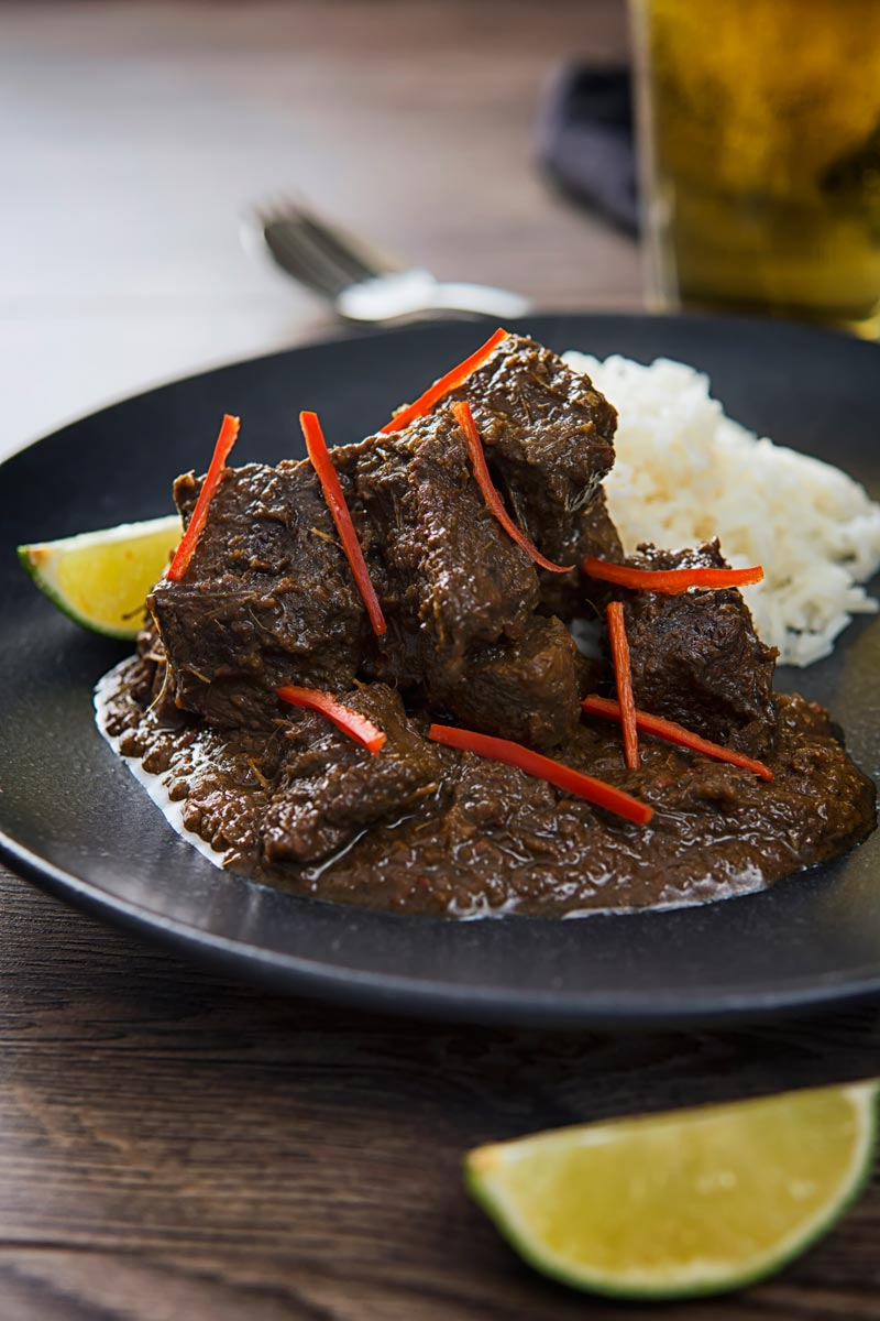Portrait image of an Indonesian Beef Rendang served on a black plate with rice, lime wedges and chilli ribbons.