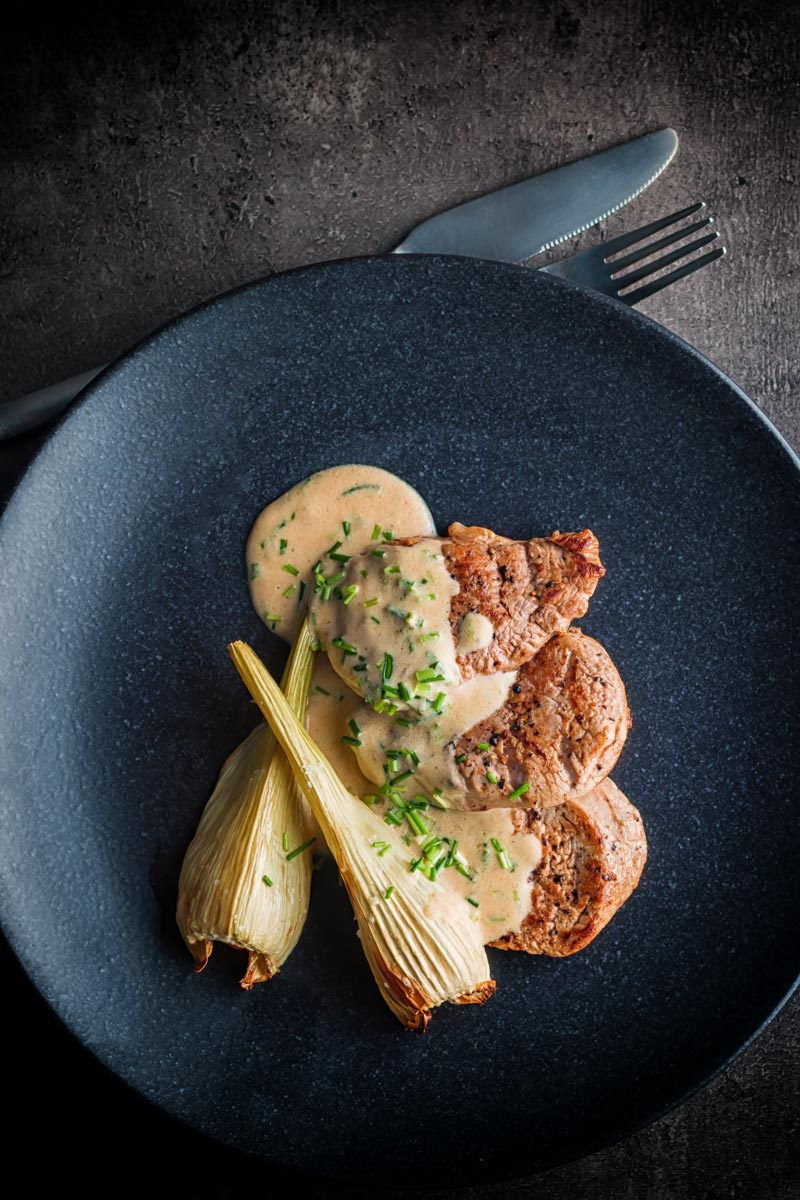Tall picture of Pan Fried Pork Tenderloin Fillet with Roasted Fennel and A Camembert and cider sauce on a black plate taken from above