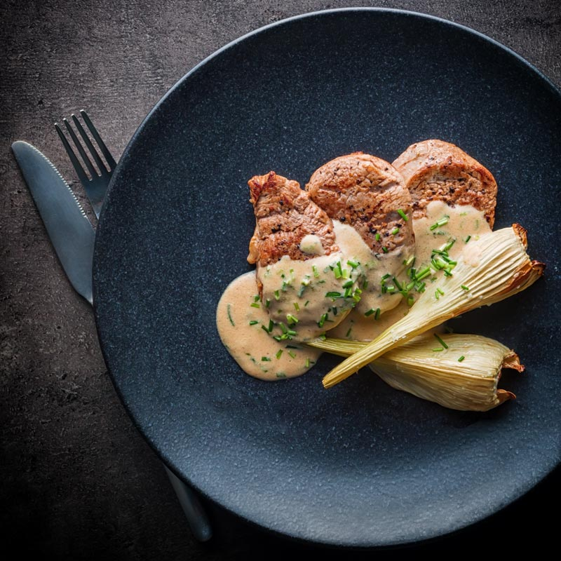 Square picture of Pan Fried Pork Tenderloin Fillet with Roasted Fennel and A Camembert and cider sauce on a black plate taken from above