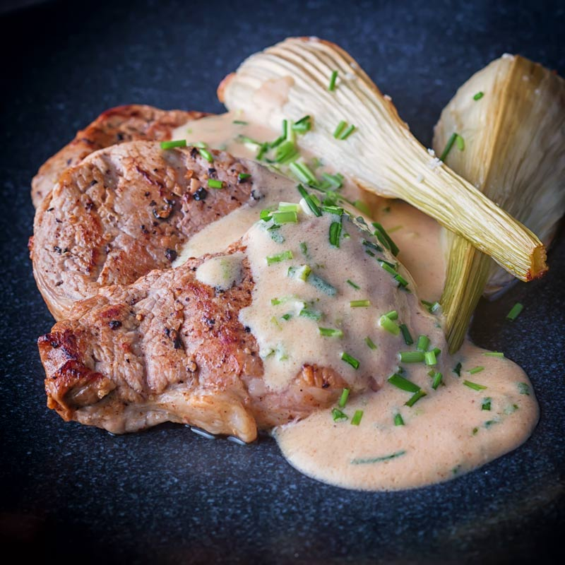 Square picture of Pan Fried Pork Tenderloin Fillet with Roasted Fennel and A Camembert and cider sauce on a black plate