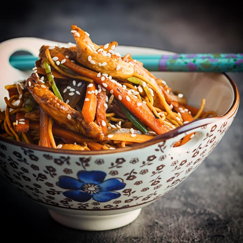 Square image of Chicken Lo Mein in an Asian style bowl with a blue flower against a dark background