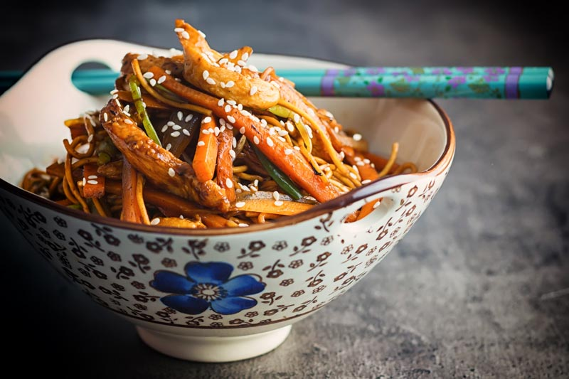 Landscape image of Chicken Lo Mein in an Asian style bowl with a blue flower against a dark background