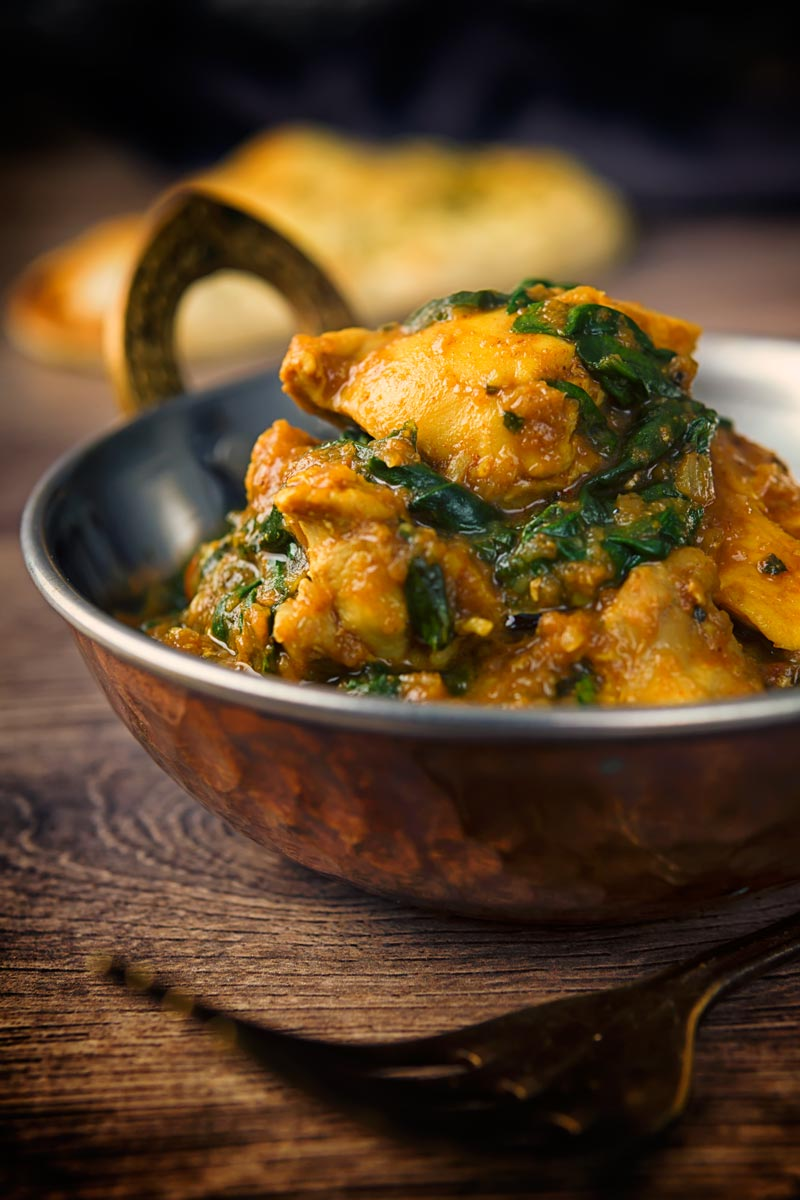 A tall image of a chicken saag curry in a 'brass' curry bowl on a wooden backdrop