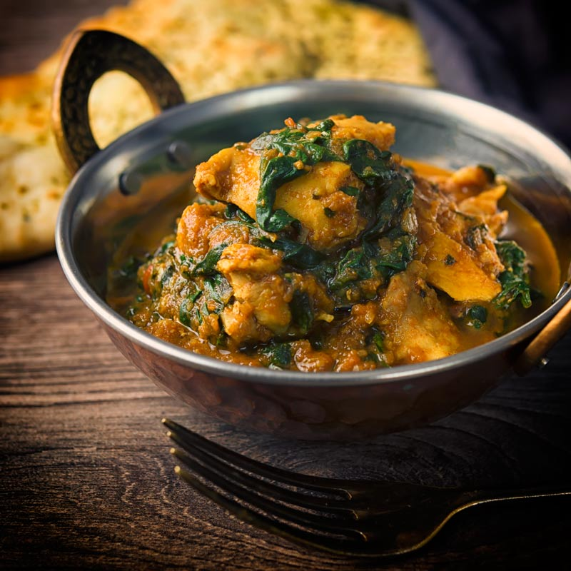 A square image of a chicken saag curry in a 'brass' curry bowl on a wooden backdrop