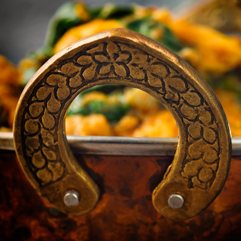 Close up image of the handle of a brass curry bowl with an out of focus curry in the background