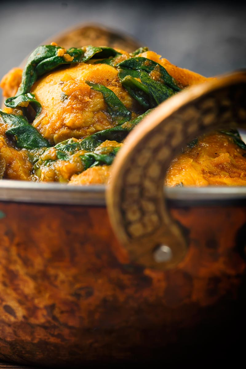 Close up image of chicken thighs and wilted spinach in a chicken saag curry in a brass curry bowl