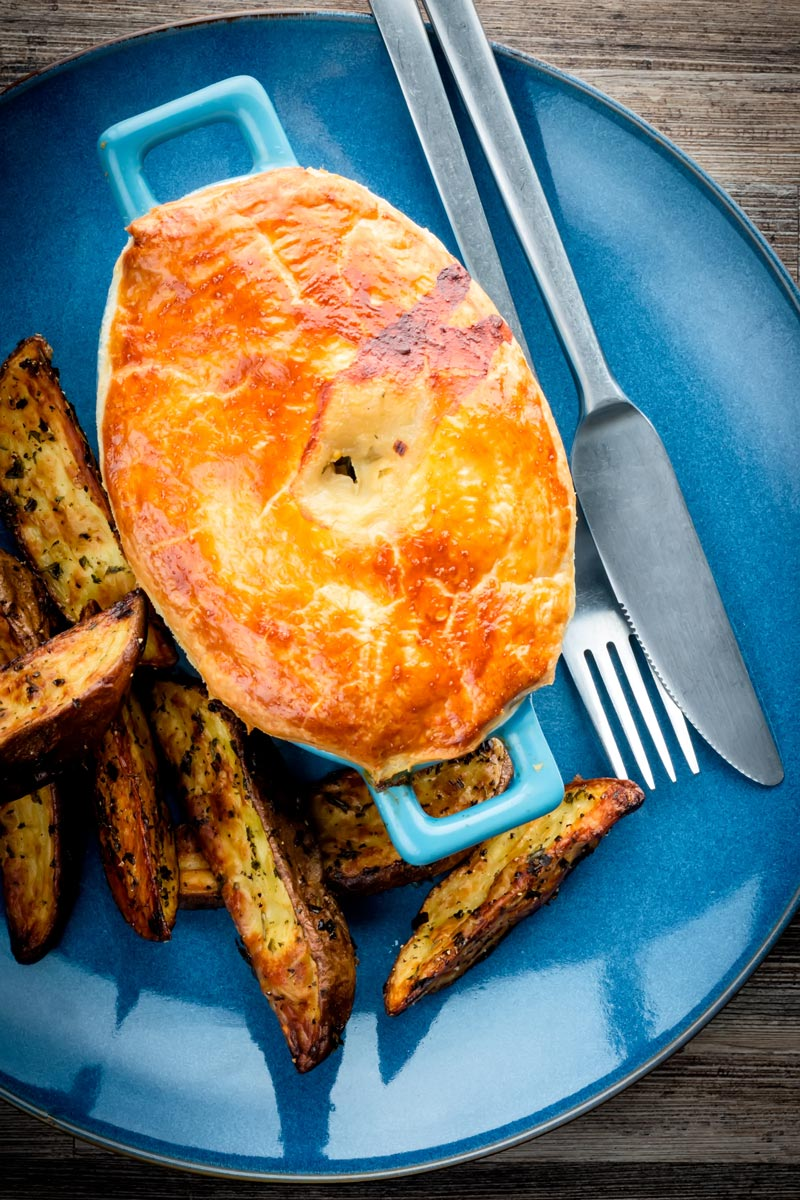 Portrait image of a Chicken and mushroom pie on a blue plate with potato wedges