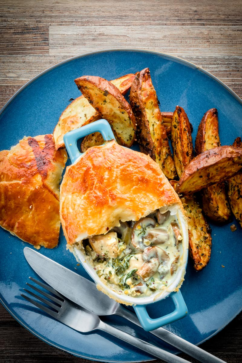 Tall image of a Chicken and mushroom pie on a blue plate with potato wedges with half of the pastry removed to expose the pie filling