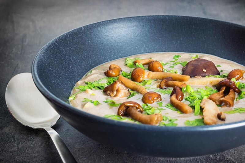 A bowl of cream of wild mushroom soup in a black bowl