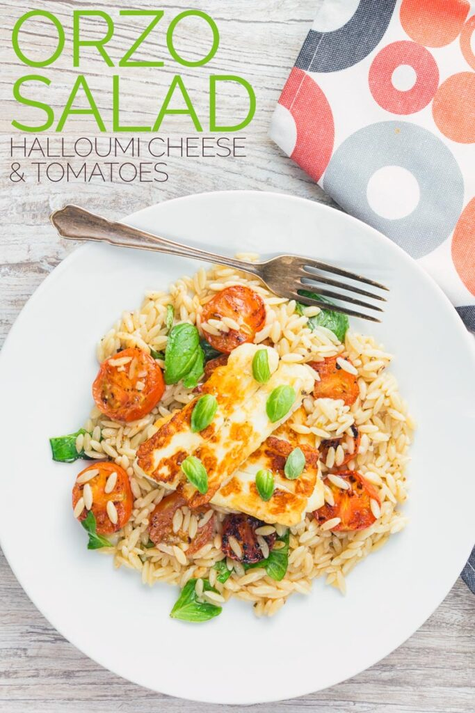 Tall overhead image of an orzo salad with seared tomatoes and seared halloumi cheese on a white plate with text