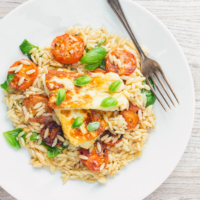 Square image of fried halloumi cheese on an orzo salad with seared tomatoes and basil taken from above