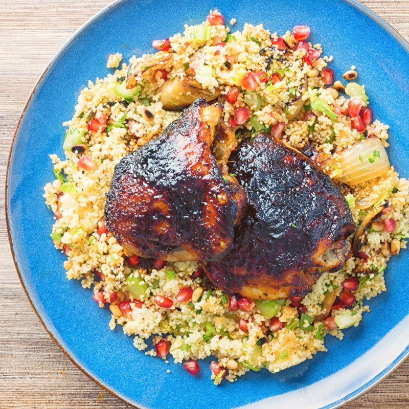 Glazed harissa chicken thighs on a bed of couscous served on a blue plate taken from above